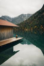 Woman Sitting On Deck By Lake ...