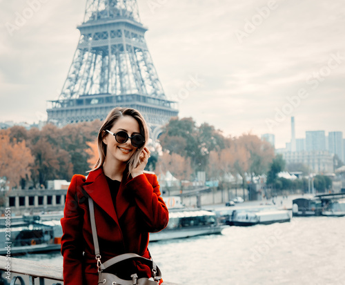 Obraz Style redhead girl in red coat make a photo on parisian street in autumn season time. Eiffel tower on background - fototapety do salonu