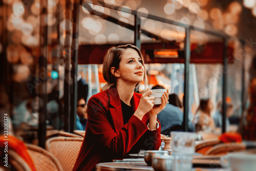 Obraz Style redhead girl in red coat with cup of coffee in parisian cafe. Autumn season time - fototapety do salonu