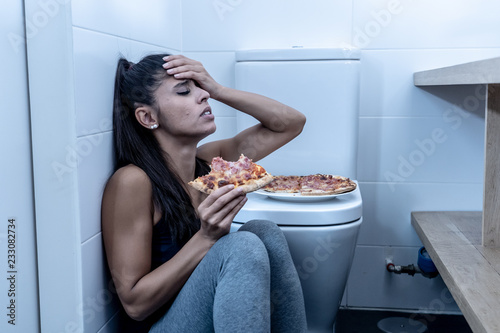 Young beautiful bulimic woman sitting on the bathroom floor eating pizza looking Wallpaper Mural