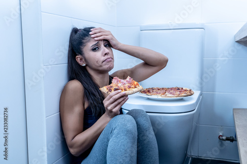 Photo Young beautiful bulimic woman sitting on the bathroom floor eating pizza looking