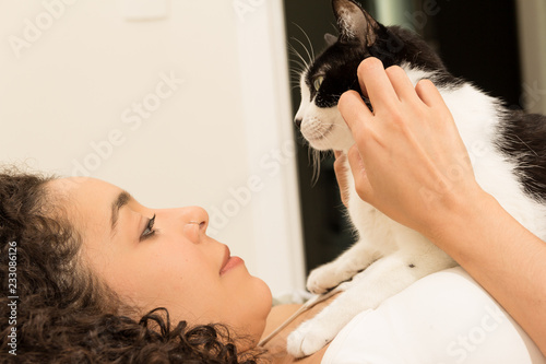 Fotografia  Girl with curly hair holding her domestic black and white cat in bed