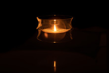 A Candle In A Glass Bowl Candle Holder Is Reflected In A Dark Reflecting Pool Of Water