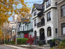 Street Of Historically Designated Old Victorian Houses With Gables And Painted Brick, Downtown Toronto, With Large Office Building In Background