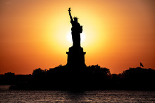 Scenic View Of Statue Of Liberty At A Sunset. Sun Behind The Statue Create Beautiful Silhouette.