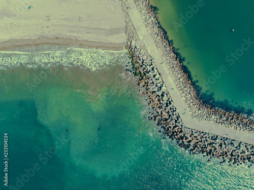 Photo  An aerial view, high up, and directly above the beach and jetty at the Santa Cru