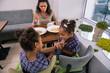 Scolding for behavior. Dark-haired caring mother scolding her little girls for bad behavior in restaurant