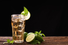 Iced Lime Tea In Glass With Mint And Slice Lime On Wooden Table And Black Background
