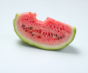 Bitten slice of watermelon on a white background..