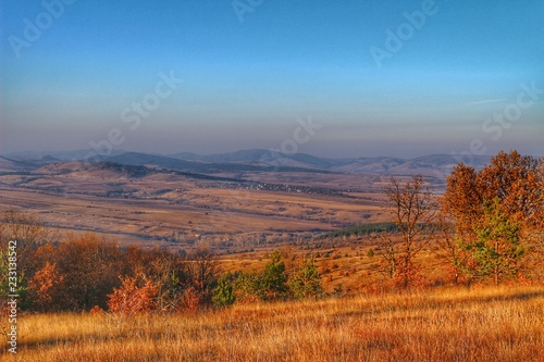 Tuinposter Baksteen A scenic panoramic view of autumn trees, grass, fields and mountains during sunset at golden hour