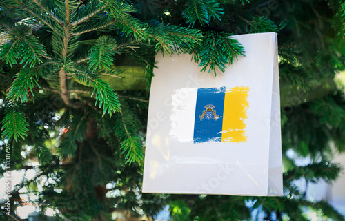 In de dag Canarische Eilanden Canary Islands flag printed on a Christmas shopping bag. Close up of a shopping bag as a decoration on a Xmas tree on a street. New Year or Christmas shopping, local market sale and deals concept.