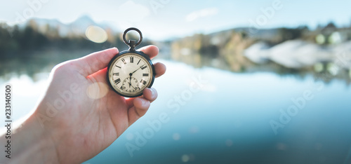 Obraz Vintage watch hand-held, autumwn view with lake and trees in the background - fototapety do salonu