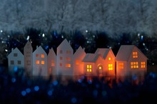 Handmade Small White Cardboard Houses With Illuminated Windows On Dark Blue Bokeh Foreground And Background. Winter Decoration. Shallow Depth Of Focus.