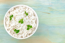 A Photo Of A Bowl Of Cooked White Long Rice, Shot From The Top On A Teal Blue Background With Copy Space