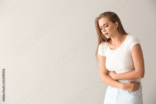 Obraz Young woman suffering from abdominal pain on light background - fototapety do salonu