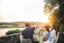 Friends Toasting Drinks At Dining Table During Sunset