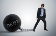 canvas print picture - Young businessman has chained big metal ball to his leg with deb