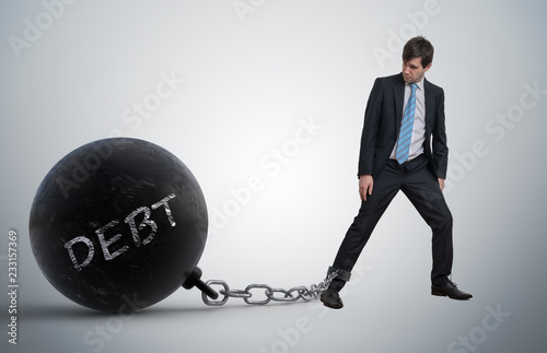 Photo Young businessman has chained big metal ball to his leg with deb