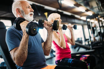 Fototapeta na wymiar Fit senior sporty couple working out together at gym