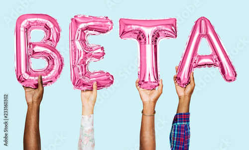 Photo Hands holding beta word in balloon letters