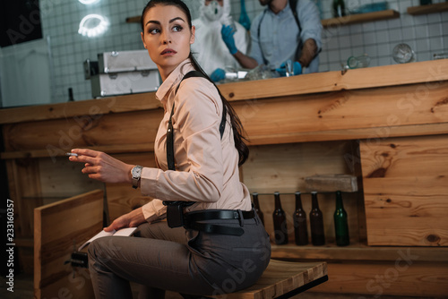 cropped view of smoking female detective sitting at crime scene with colleagues Fototapeta