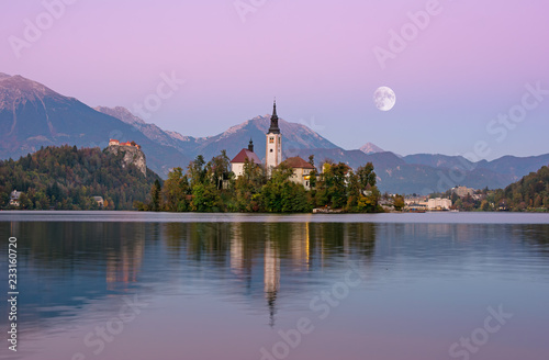 Foto auf AluDibond Flieder Beautiful sunrise landscape of lake Bled in Slovenia with church on green island and moon on purple sky