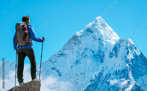 Photo Hiker with backpacks reaches the summit of mountain peak