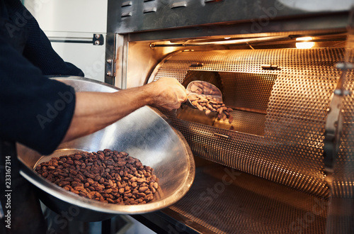 Fotografía Chocolate making factory worker putting cocoa beans into a roaster