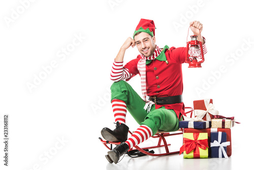 Photo  man in christmas elf costume sitting on sleigh near pile of presents and holding