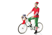 Man In Christmas Elf Costume Riding Bike With Basket Full Of Presents Isolated On White