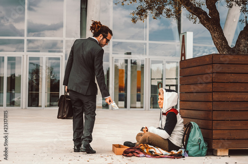 Photo Generous businessman helping a homeless on the street