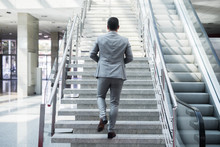 Ambitious Businessman Going Up Staircase. Back Turned.