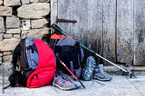 Backpacks, boots and canes with old wooden door, Camino de Santiago Canvas Print