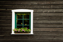 White Window With Flowers And Green Frame On A Countryside House Or Cottage With Dark Black Wooden Wall.