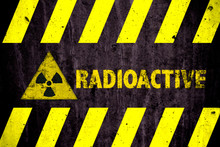 Radioactive (ionizing Radiation Or Nuclear Energy) Danger Symbol And Word With Yellow And Hazard Black Stripes Painted On A Massive Concrete Wall With Rustic Texture Background.