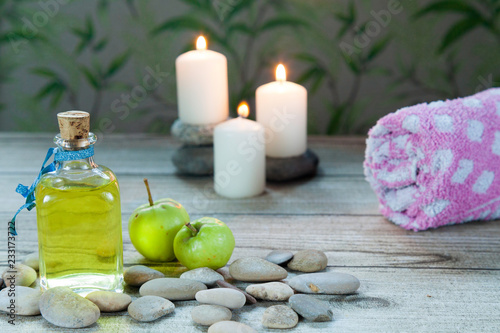Fotografía  bottle of apple oil massage, river pebbles and two small green apples