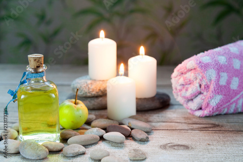 Fotografía  bottle of  oil massage, river pebbles and a small green apple