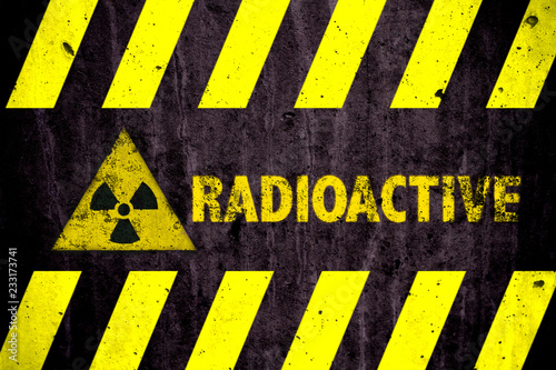 Cuadros en Lienzo Radioactive (ionizing radiation or nuclear energy) danger symbol and word with yellow and hazard black stripes painted on a massive concrete wall with rustic texture background