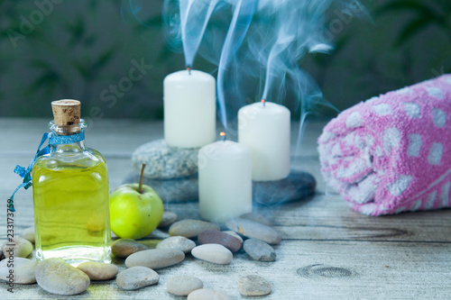 Fotografía  bottle of  oil massage, candles with smoke and  green apple