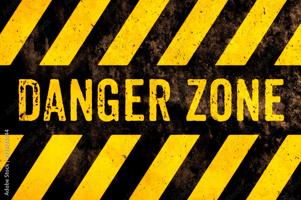 Fototapeta Danger zone warning sign text with yellow and black stripes painted over concrete wall surface facade cement texture background. Concept image for caution, risky dangerous area and hazard.