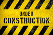 canvas print picture Under construction warning sign text with yellow black stripes painted over concrete wall cement facade as texture background. Concept for do not enter the area, caution, danger, construction site.