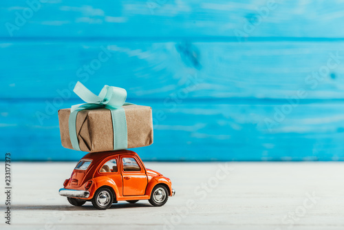 Photo  close-up shot of toy vehicle with gift box on blue wooden background