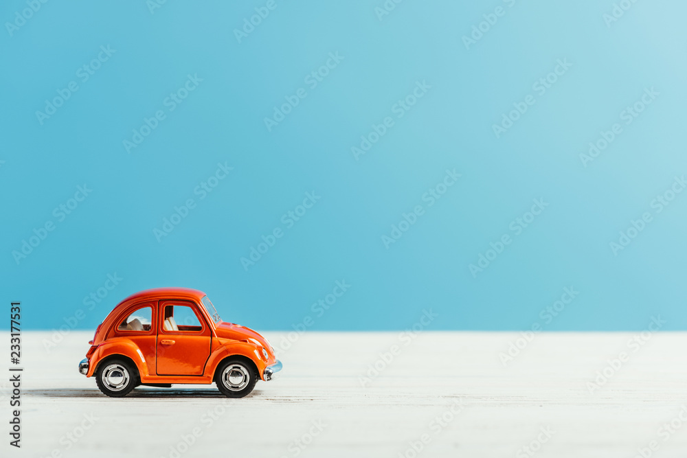 Fototapety, obrazy: side view of toy red car riding on white surface on blue background