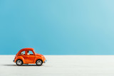 side view of toy red car riding on white surface on blue background
