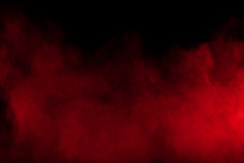Red Powder Explosion On Black Background. Freeze Motion Of Red Dust Particles Splash.