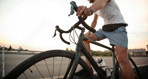 Foto op Plexiglas Fietsen The young guy in casual clothes is cycling on the road in the evening city