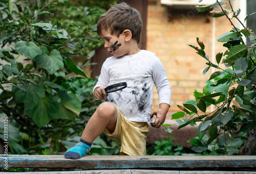 Fotografía  Little toddler boy with dirty face and dirty clothes looking through a magnifying glass on nature