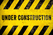 canvas print picture Under construction warning sign text with yellow black stripes painted over concrete wall cement facade texture background. Concept for do not enter the area, caution, danger, construction site