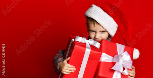 Fotomural Funny smiling child in Santa red hat holding Christmas gift in hand