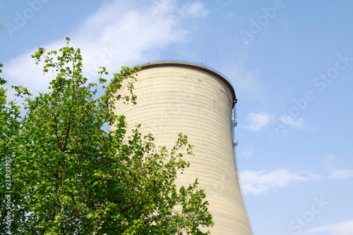 Fotografía  heavy industrial water cooling tower and the green tree